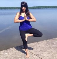 Picture of Yoga teacher, Miss Deepa in a yoga pose in front of a lake